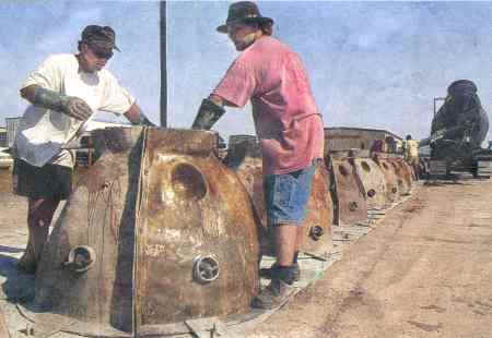 "larry.jpg - Larry Beggs, above left, and Shawn Trew pack concrete into a ""reef ball"" mold at Wanchese Seafood Industrial Park on Monday Sept 11, 2000."